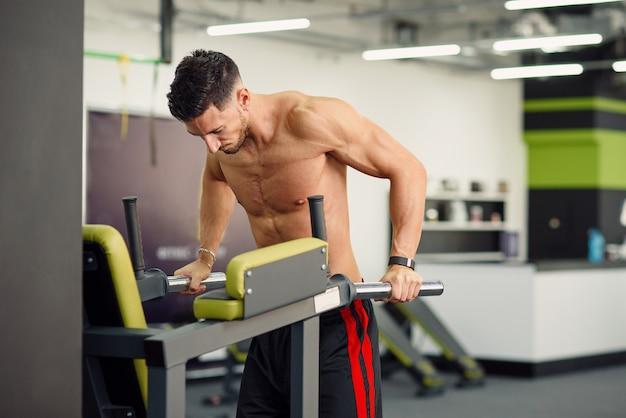 Sportlicher fitness-mann, der liegestütze auf barren während des trainings im modernen fitnessstudio tut. gesundes und sportliches konzept.