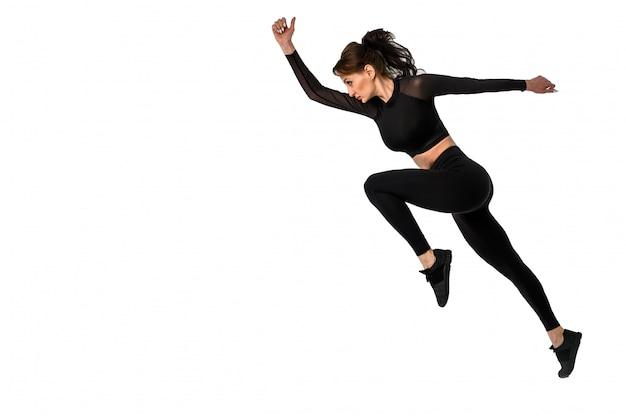 Sportlicher frauenläufer in der silhouette auf weißem hintergrund. attraktive frau in modischer sportbekleidung. dynamische bewegung. seitenansicht.