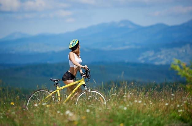 Sportlicher frauenreiter, der talblick mit mountainbike unter gras genießt
