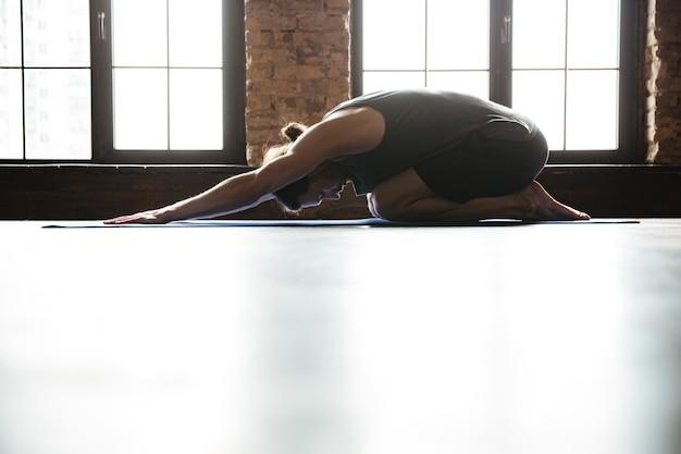 Sportlicher gesunder mann, der vor dem training im fitnessstudio zurückreicht