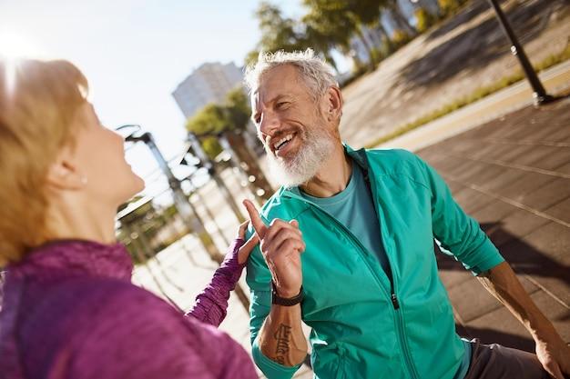 Sportlicher glücklicher reifer mann, der etwas mit seiner frau bespricht, während er früh zusammen trainiert
