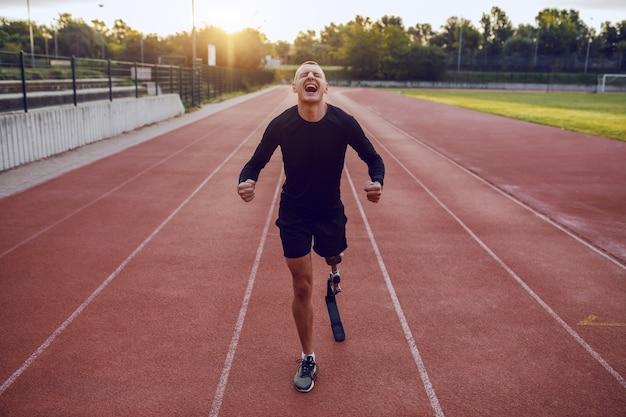 Sportlicher gutaussehender kaukasischer behinderter mann mit künstlichem bein, das auf rennstrecke steht und sich zum laufen motiviert.