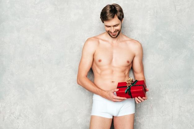 Sportlicher gutaussehender starker mann. gesundes sportliches fitnessmodell, das in der nähe der grauen wand in weißer unterwäsche posiert.