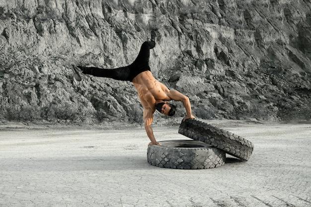 Sportlicher hemdloser mann in der schwarzen gesichtsmaske, die liegestütze auf schweren reifen während des trainings im sandsteinbruch tut. konzept des aktiven und gesunden lebensstils.