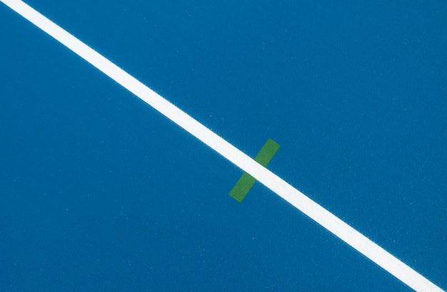 Sportlicher hintergrund. blaue laufbahn mit weißen linien und grüner markierung im sportstadion. draufsicht