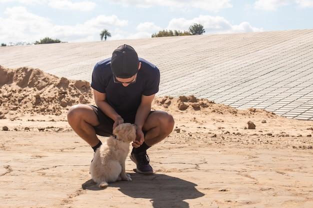 Sportlicher junge, der seinen welpen im sand streichelt.