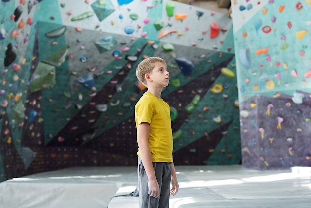 Sportlicher junge in aktivkleidung, der in der mitte des raumes zum klettern steht und eine der wände betrachtet