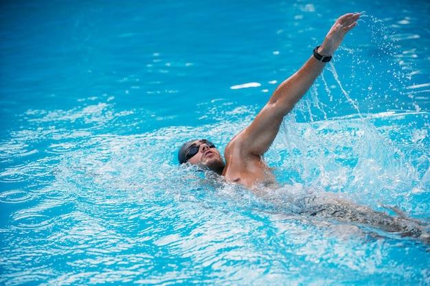 Sportlicher junger mann, der auf rückenschwimmenart schwimmt. schwimmwettbewerb.