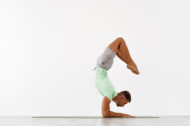 Sportlicher junger mann, der backbend-handstand-yoga pilates-fitnesstraining im kinn-balance-asana macht