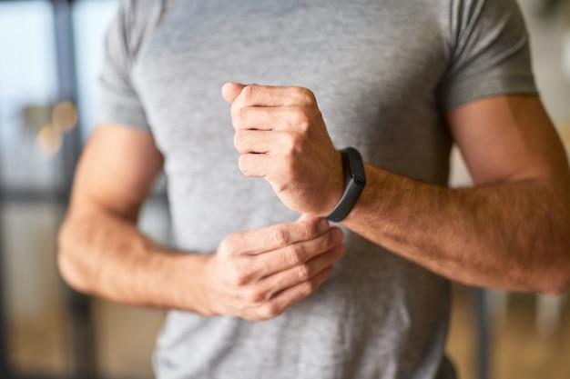 Sportlicher junger mann, der eine smartwatch am handgelenk anzieht