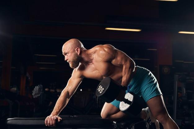 Sportlicher junger mann, der gewichte hebt, während er eine körperliche übung in einem fitnessstudio macht