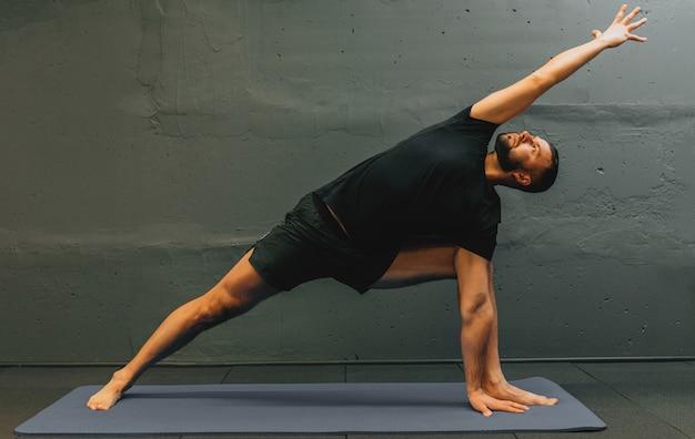 Sportlicher junger mann, der handstand yoga macht. studioaufnahme im städtischen fitnessstudio mit grauem hintergrund für kopierraum.
