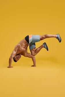 Sportlicher junger mann, der handstandübungen macht