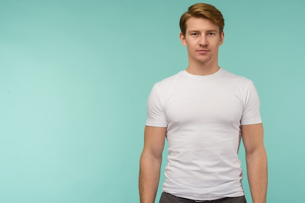 Sportlicher junger mann, der im weißen t-shirt auf blauem hintergrund steht.