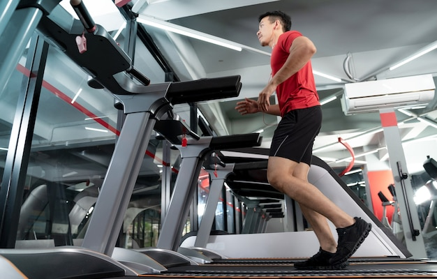 Sportlicher junger mann, der läuft und musik von seinem smartphone im fitnessstudio hört