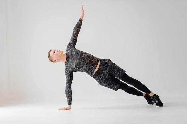 Sportlicher junger mann, der zu hause trainiert, mann, der trainiert, sich vor dem krafttraining aufwärmt.