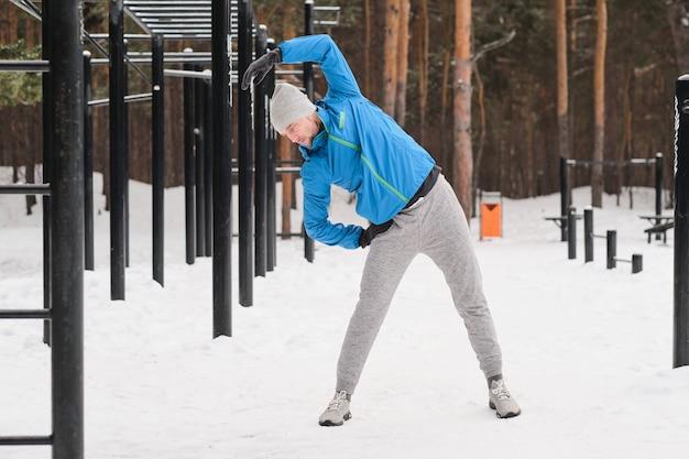 Sportlicher junger mann im hut, der im winter am trainingsbereich steht und aufwärmübung tut