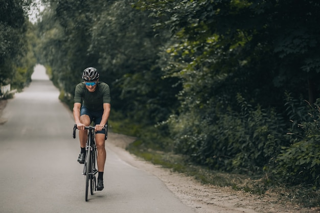 Sportlicher junger mann in activewear, schutzhelm und verspiegelter brille, der fahrrad auf der straße fährt. kaukasischer radfahrer mit muskulösen beinen, der hartes und aktives training an der frischen luft hat.