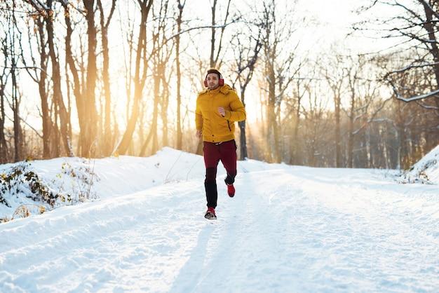 Sportlicher junger mann in sportbekleidung mit kopfhörern, die auf schneebedeckter winterstraße am morgen nahe dem wald laufen.