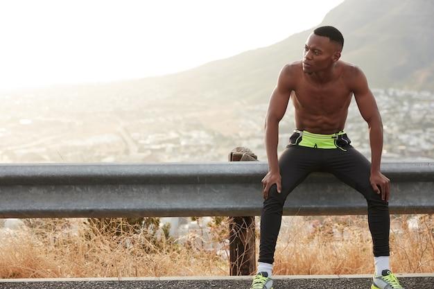 Sportlicher junger mann läuft mit geschwindigkeit, hat pause nach dem training im freien in der nähe von bergen, bereitet sich auf sportturniere vor, hat regelmäßige gymnastikübungen, freizeit im freien. gesunder lebensstil