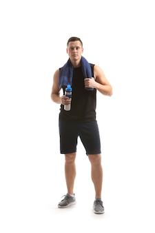 Sportlicher junger mann mit flasche wasser gegen weiße oberfläche