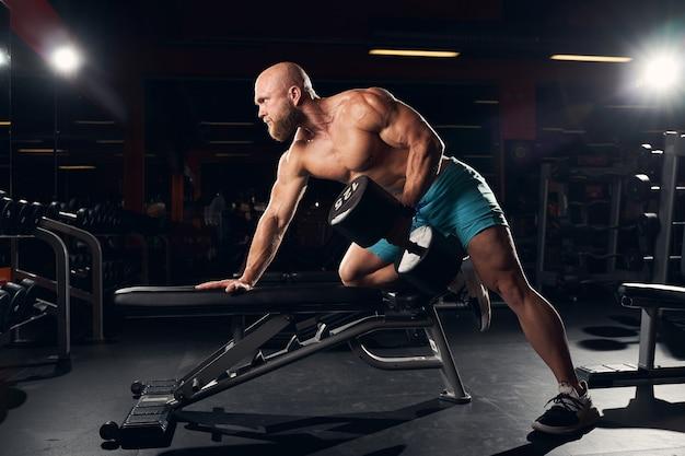 Sportlicher junger sportler, der fit bleibt, während er im fitnessstudio gewichte hebt
