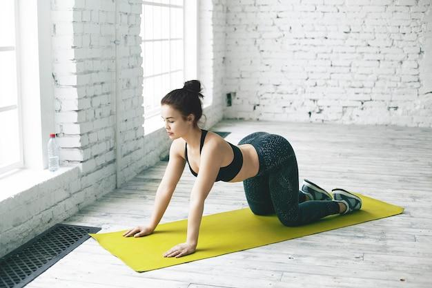 Sportlicher junger weiblicher yogi im trendigen schwarzen sportoutfit, das wirbelsäule aufwärmt und kuhasana tut. flexibles mädchen, das yoga-backbends im geräumigen raum mit weißer backsteinkopierraumwand für ihren text praktiziert