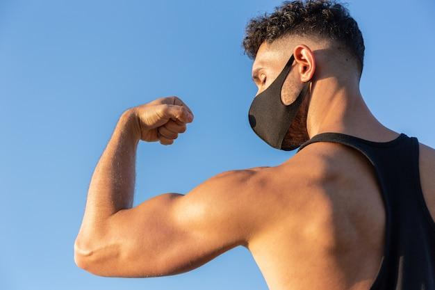 Sportlicher kaukasischer mann, der gesichtsmaske trägt, die seinen bizeps auf blauem himmelhintergrund zeigt. konzept des kampfes gegen covid-19 coronavirus. speicherplatz kopieren