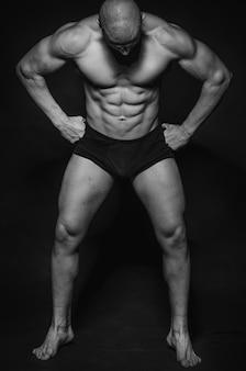 Sportlicher kerl, der auf weißer wand aufwirft. sport, schönheit, schwarzweißfotografie.