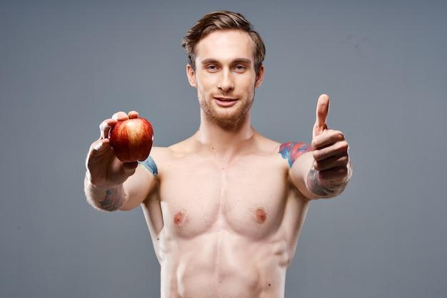 Sportlicher kerl mit einem aufgepumpten oberkörper gesunder lebensstil ernährung vitamine roter apfel