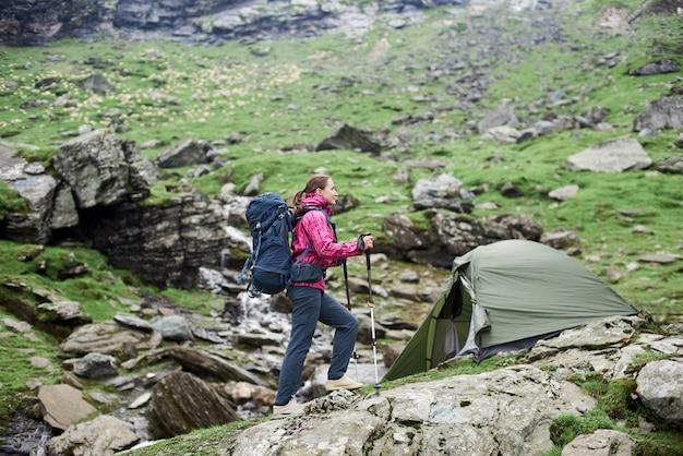 Sportlicher kletterer der frau, der den felsigen hang der schönen berge hinaufgeht