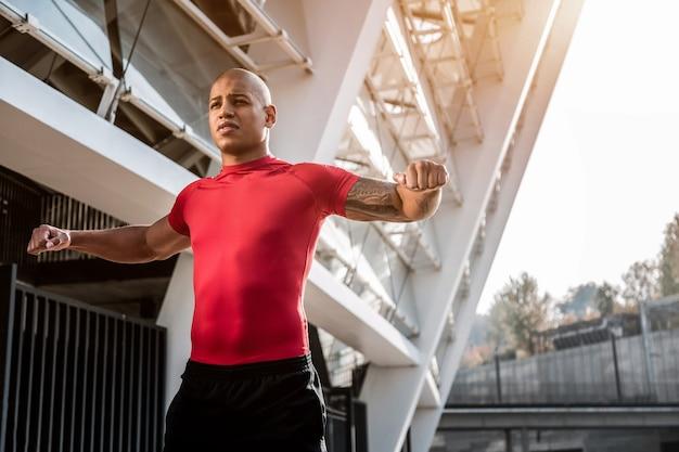 Sportlicher lebensstil. gut gebauter junger mann, der sportliche aktivitäten im freien ausführt