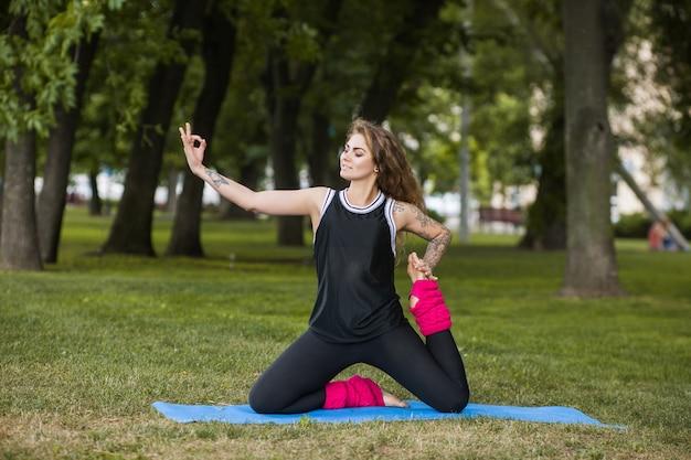 Sportlicher lebensstil. outdoor-yoga. frau macht übungen im park
