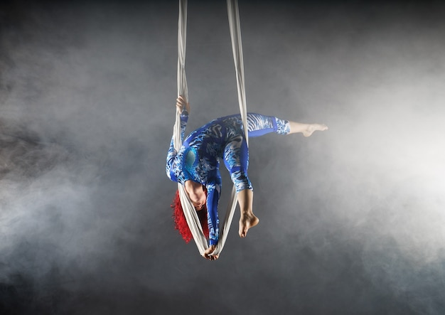 Sportlicher luftzirkuskünstler mit rotschopf im blauen kostüm, der auf einer hand in der luftseide steht Premium Fotos