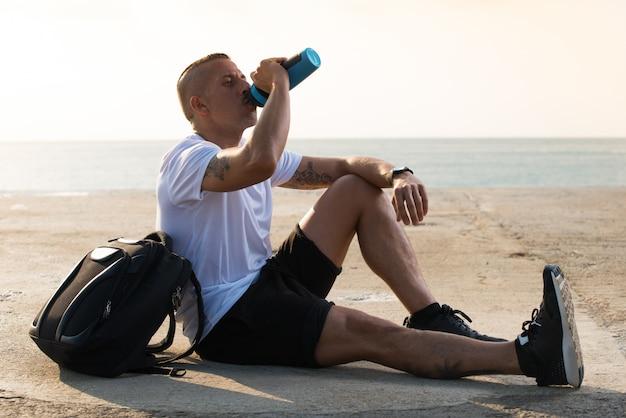 Sportlicher männlicher athlet, der durstig ist