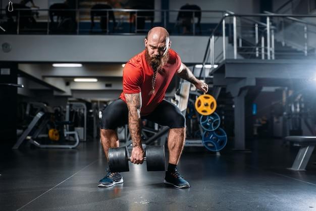 Sportlicher männlicher lifter, der übung mit hanteln im fitnessstudio tut. bärtiger sportler im sportverein, gesunder lebensstil