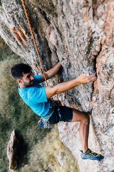 Sportlicher mann auf felsen klettern