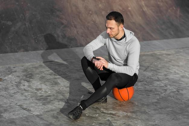 Sportlicher mann, der auf einem basketball stillsteht