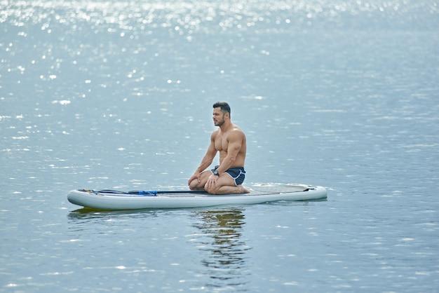 Sportlicher mann, der auf sup brett während des trainierens auf see sitzt und vorwärts schauen.