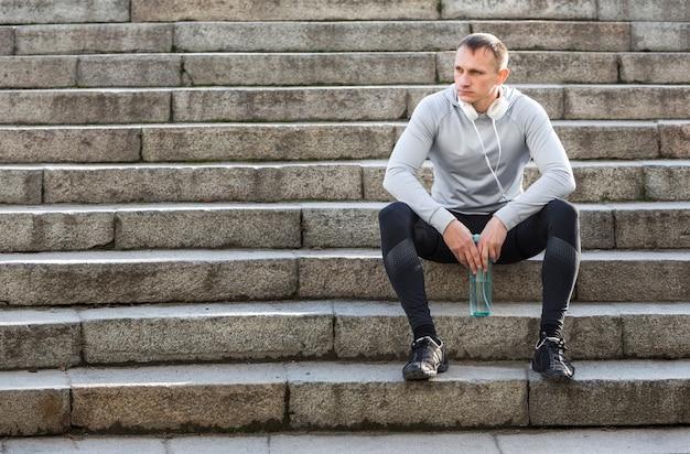Sportlicher mann, der auf treppe stillsteht und weg schaut