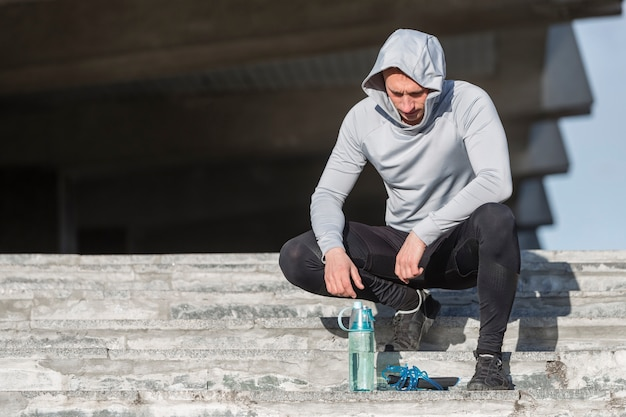 Sportlicher mann, der auf treppen sitzt und eine flasche wasser betrachtet