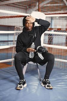 Sportlicher mann, der boxt. foto des boxers auf einem ring. afroamerikaner mann ausbildung.