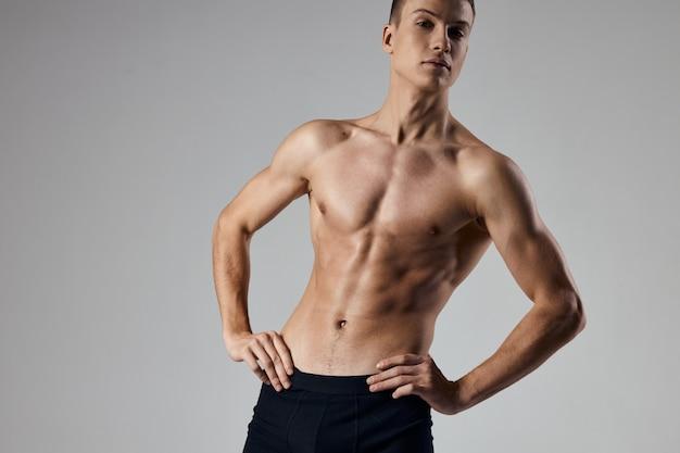Sportlicher mann, der die hände am gürtel auf grauem hintergrund hält, beschnittenes ansichtsmodell