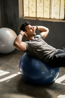 Sportlicher mann, der die sit-ups auf einem balanceball macht