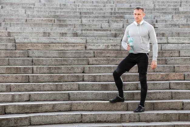 Sportlicher mann, der eine flasche wasser auf treppen hält