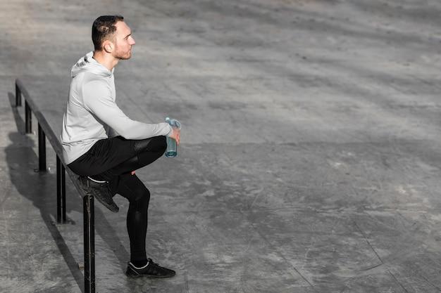 Sportlicher mann, der eine flasche wasser stillsteht und hält