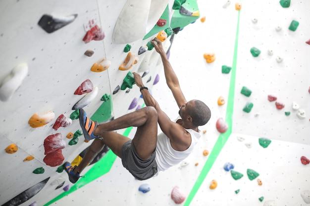 Sportlicher mann, der eine wand in einem kletterzentrum klettert