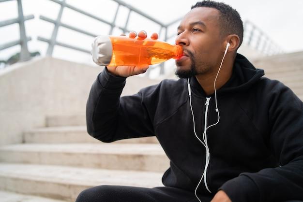 Sportlicher mann, der etwas nach dem training trinkt.