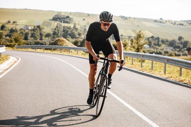 Sportlicher mann, der fahrrad mit hintergrund der natur reitet