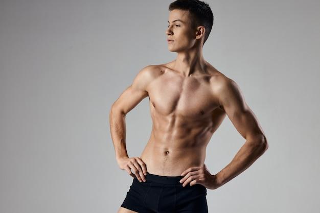 Sportlicher mann, der hände auf gürtel auf grauem hintergrund beschnittene ansicht hält